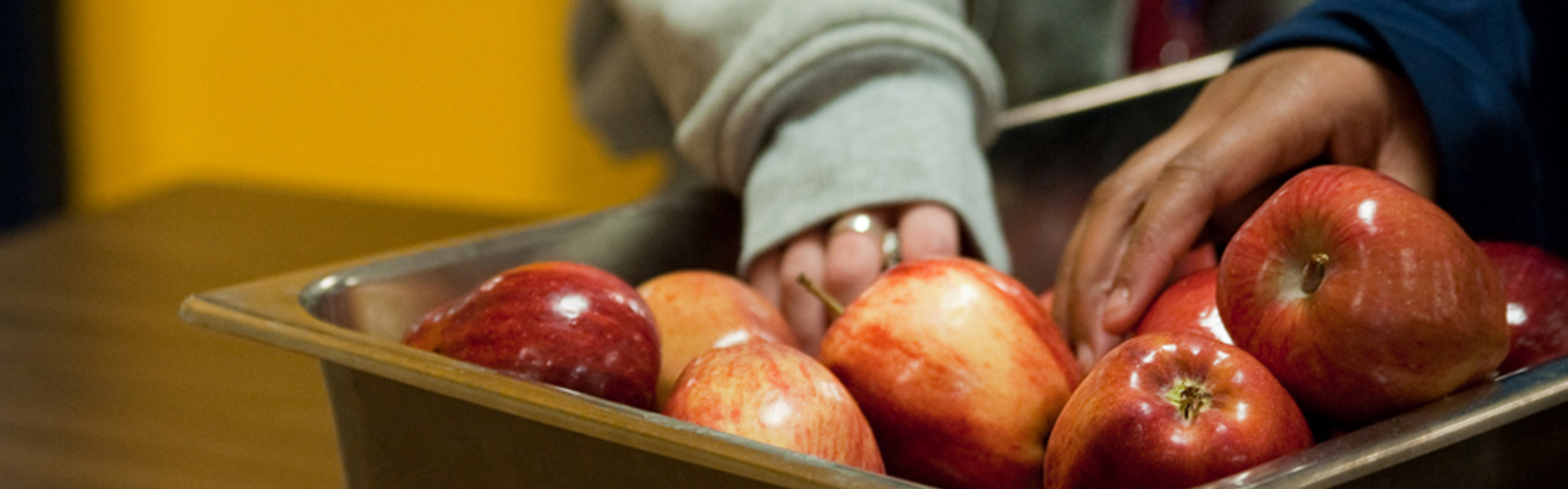 Children's Hands reaching into a bin full of red apples