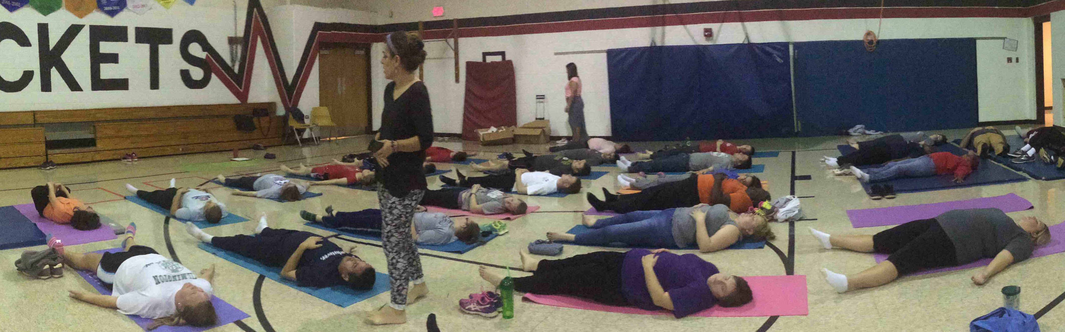People lying on yoga mats in a gymnasium