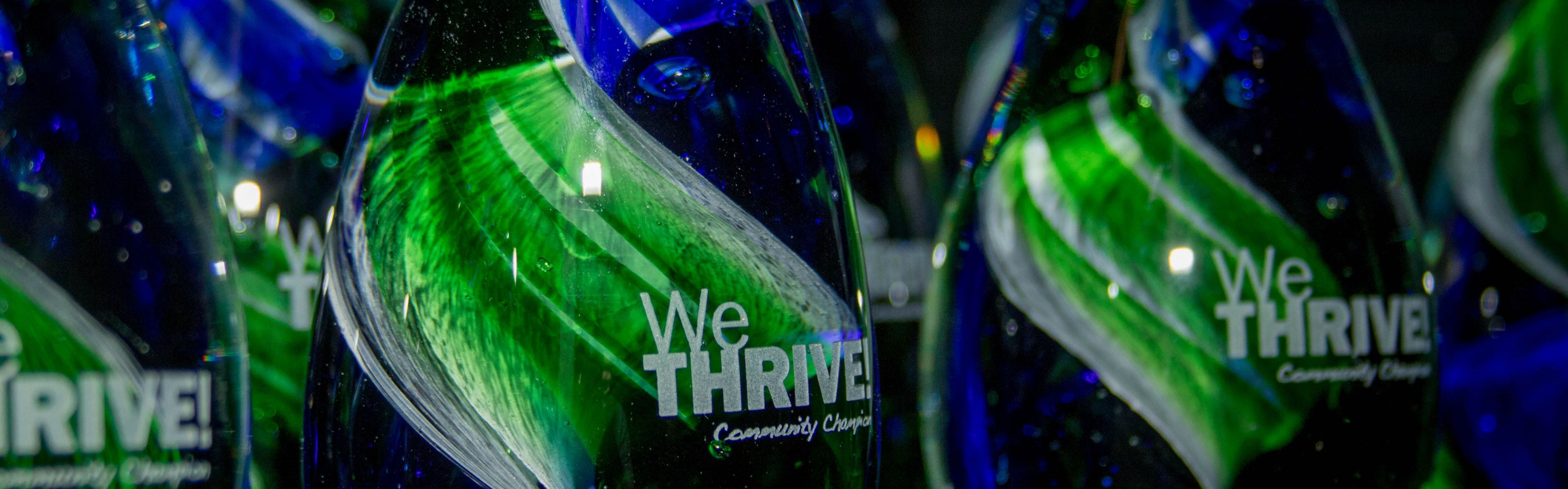 blue and green awards that say we thrive community champion