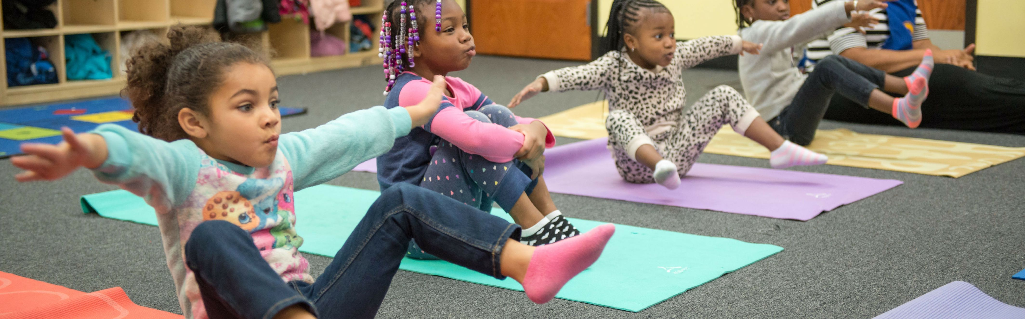 Three preschool age girls doing yoga pose on yoga mats.