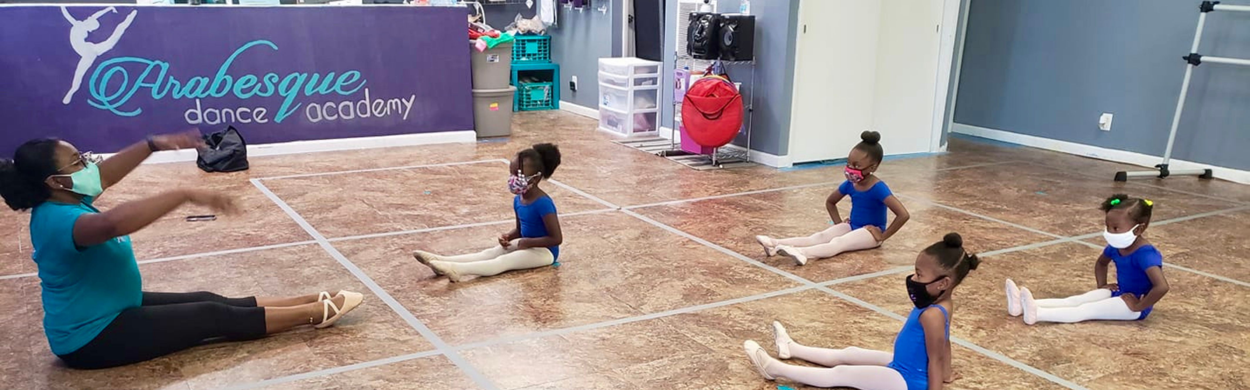 young ballet dancers sitting on floor warming up with instructor